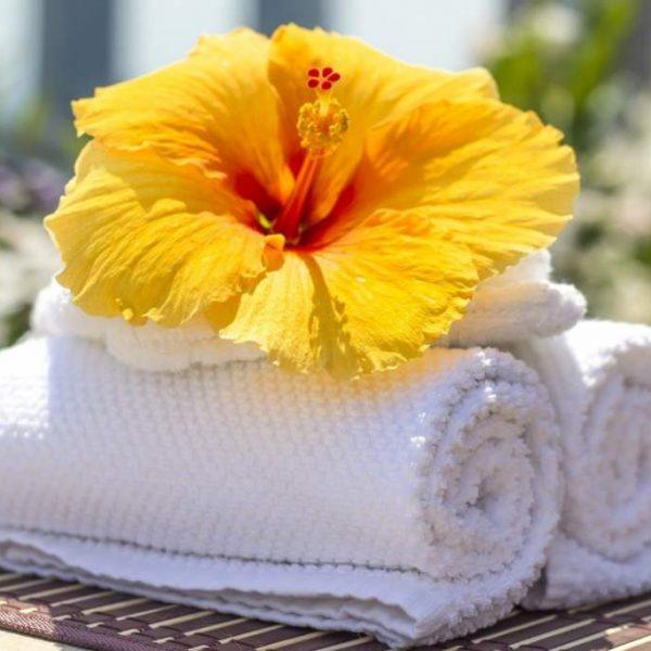 Wyprane białe ręczniki i kwiat jako symbole zapachu czystości